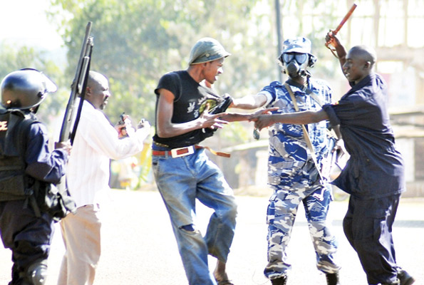 A military police officer lashes suspected protesters in Kampala during the walk-to-work protests in Kampala: Google photos