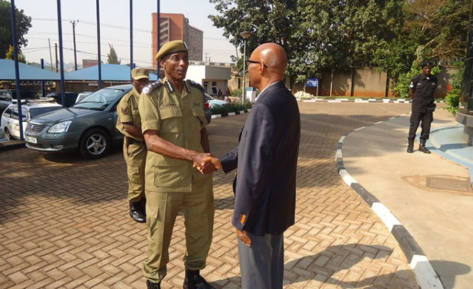 Kale-Kayihura-shakes-hands-with-UCC-executive-director-Godfrey-Mutabazi